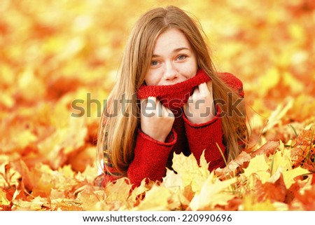 Young woman lying down in autumn leaves smiling.