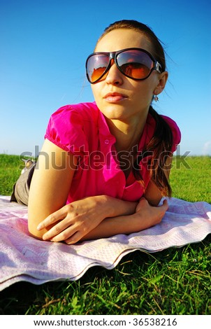 Young woman lying down on grass - stock photo