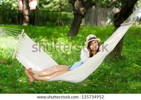 Young woman lying down on hammock - stock photo