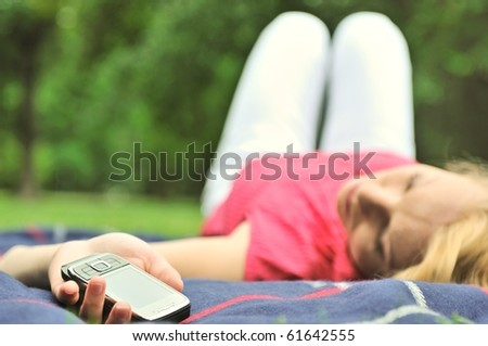 Young woman lying down on rug outdoors with mobile phone in stretched hand - stock photo