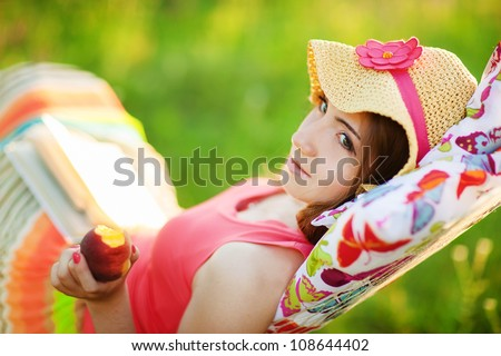 Young woman lying in a hammock in garden and reading a book and eating peach - stock photo