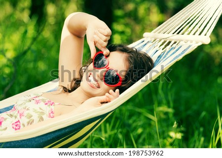 Young woman lying in a hammock in garden with heart shaped sunglasses. - stock photo