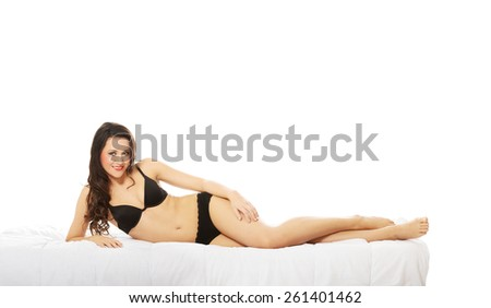 Young woman lying in bed only in underwear