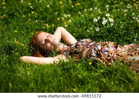 Young woman lying in grass dreaming summer day - stock photo