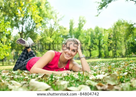 young woman lying in park and reading
