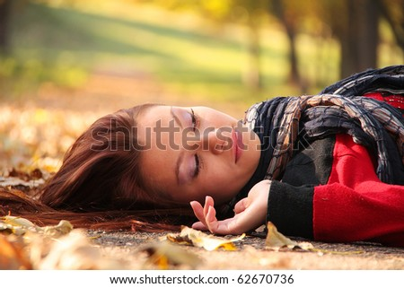 Young woman lying in the october park