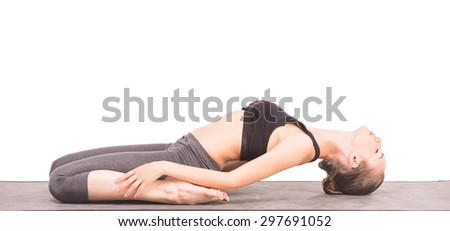 Young woman lying in yoga pose on mat. Side view. - stock photo