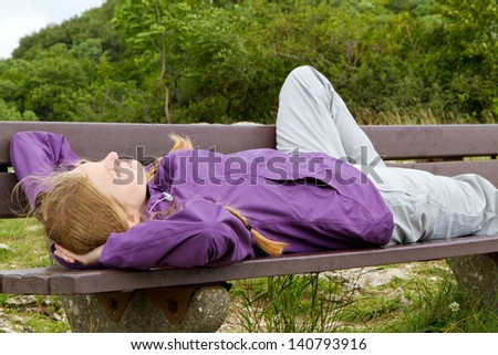 Young woman lying on a bench in nature - stock photo