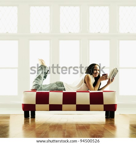 Young woman lying on a couch reading a book - stock photo