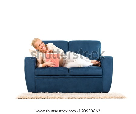 Young woman lying on a sofa eating popcorn - stock photo
