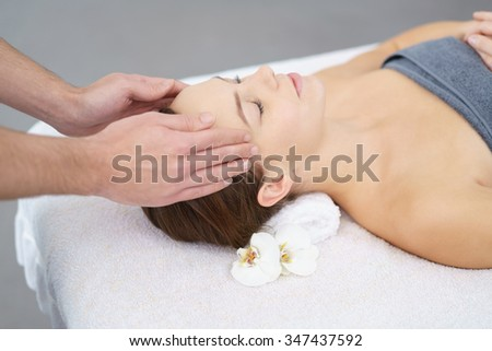 Young Woman Lying on Bed and Enjoying a Head Massage with eyes closed - stock photo