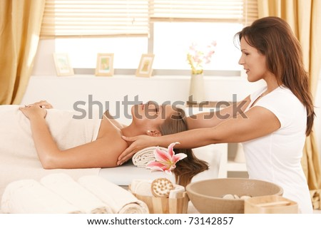 Young woman lying on bed in day spa, getting massage.?