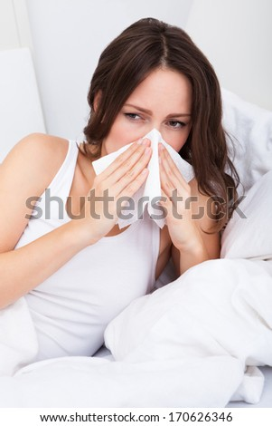 Young Woman Lying On Bed Infected With Allergy Blowing Her Nose - stock photo