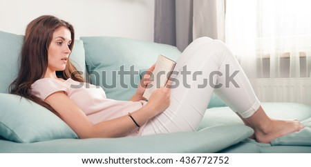 Young woman lying on couch and reading a book at home, casual style indoor shoot