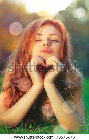 Young woman lying on grass and showing heart shape portrait. - stock photo