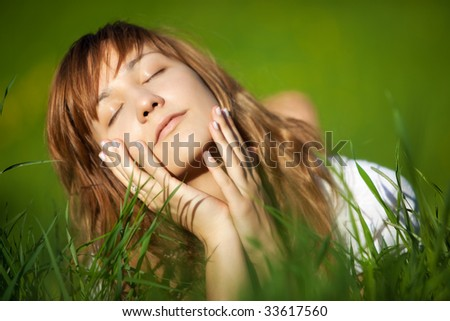 Young woman lying on grass. Shallow dof.