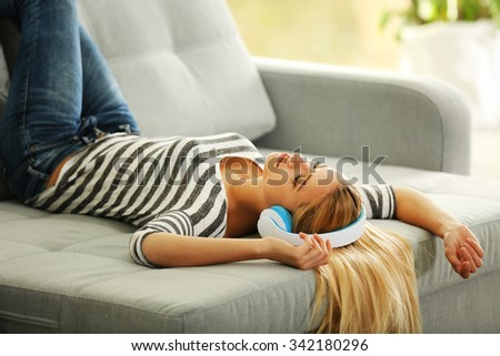 Young woman lying on sofa and listening to music - stock photo