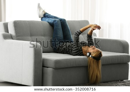 Young woman lying on sofa and listening to music