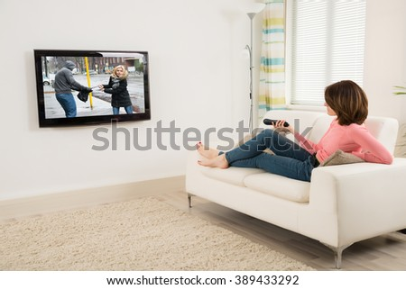 Young Woman Lying On Sofa Holding Remote While Watching Television