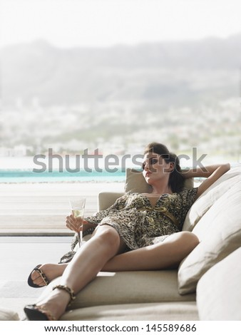 Young woman lying on sofa with champagne against balcony - stock photo