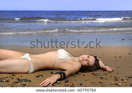 Young woman lying on the beach - stock photo