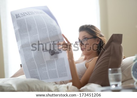 Young woman lying on the bed at home and reading the newspaper  - stock photo