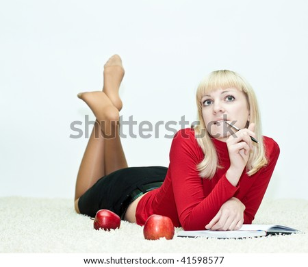 Young woman lying on the floor and writing in a diary - stock photo