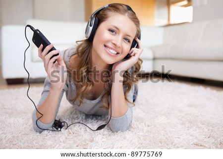 Young woman lying on the floor enjoying music - stock photo
