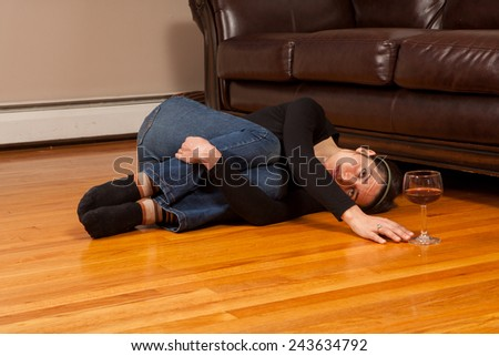 Young woman lying on the floor reaching for a wine glass - stock photo