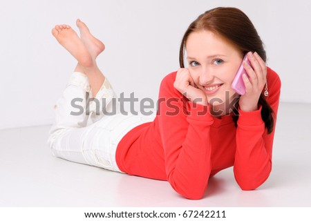 Young woman lying on the floor with cell - stock photo