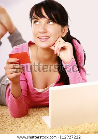 Young woman lying on the floor with credit card