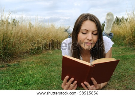 Young woman lying on the grass and reading book outdoor - stock photo