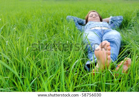 Young woman lying on the grass in the park - stock photo