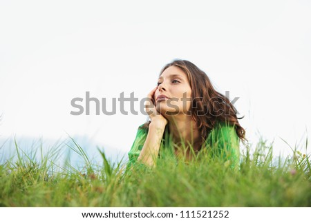 Young woman lying on the grass looking at the sky - stock photo