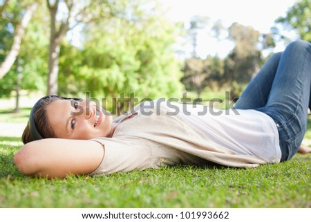 Young woman lying on the grass while listening to music