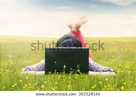Young woman lying on the green meadow while using laptop computer, shot at springtime - stock photo