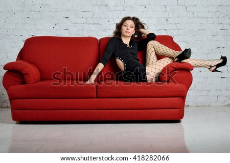Young woman lying on the red sofa.Sexy young woman in a black dress.Woman with long hair. Attractive woman in high heels. Beautiful and young woman posing on a red couch.  - stock photo