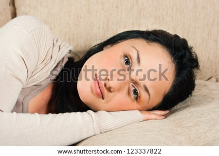 Young woman  lying on the sofa and looking at camera,Beautiful young woman - stock photo