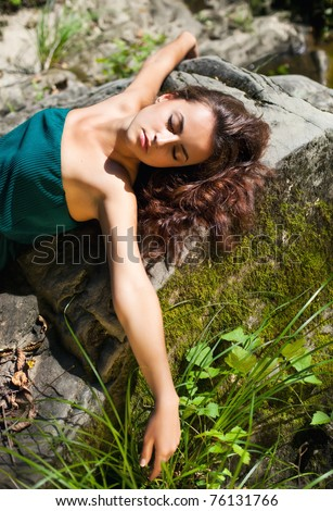 Young woman lying on the stones with arms outstretched - stock photo