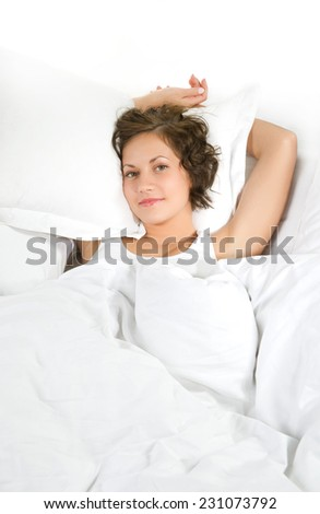 Young woman lying on white bed linen, isolated on white background
