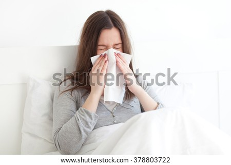 Young woman lying sick in bed - stock photo