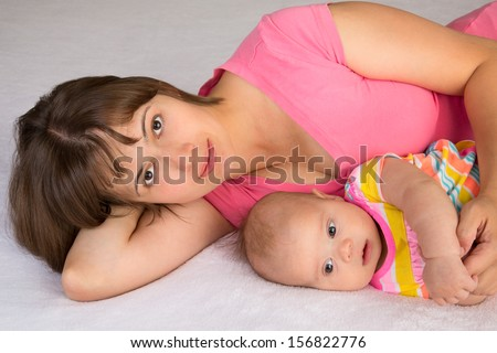 Young woman lying with her baby daughter on a terry sheet - stock photo