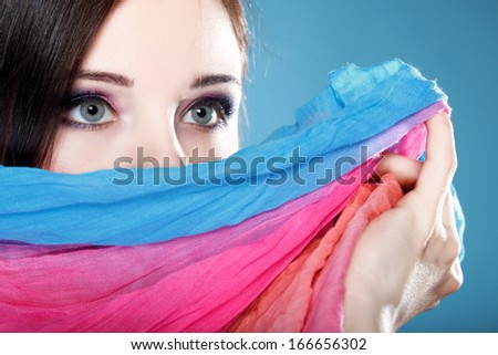 Young woman make up on eyes hides her face with multicolored shawl blue background - stock photo