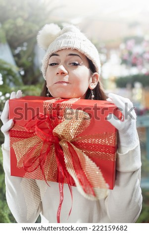 young woman makes a funny face and clenches her gift