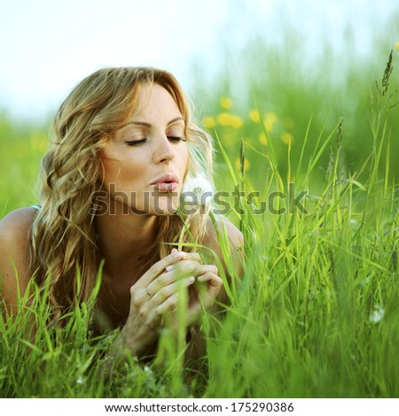 Young woman makes a wish blowing on dandelion - stock photo