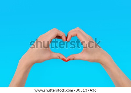 Young woman makes heart using fingers on light background