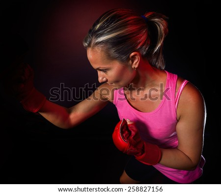 Young woman making a hard punch during training - stock photo