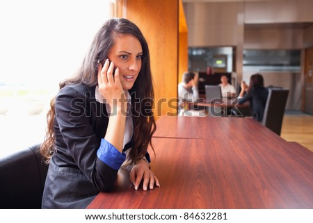 Young woman making a phone call while her coworkers are in a meeting - stock photo