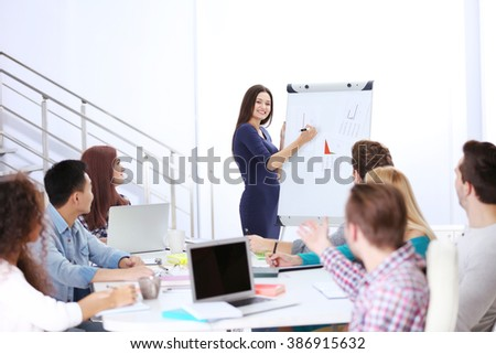 Young woman making a presentation on a board in the office - stock photo