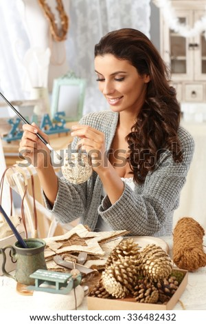 Young woman making christmas ornaments by hand, painting in vintage home. - stock photo